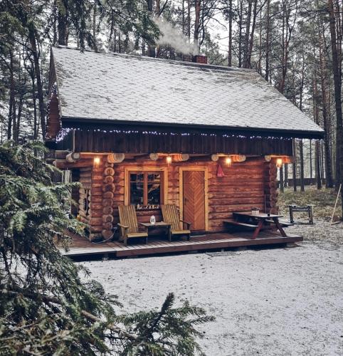 Priežu meža ieskautā mājiņa ziemas noskaņās